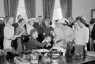 President Kennedy hands out pens at the White House signing of the Equal Pay Act on June 10, 1963.  Image by © Bettmann/CORBIS