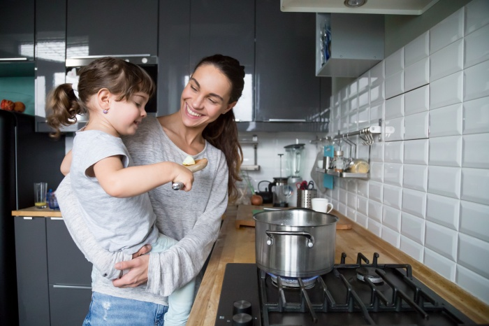 Smiling mom holding kid daughter curious about cooking in kitche